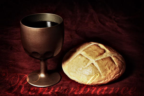 Communion elements represented by bread and wine over a red background
